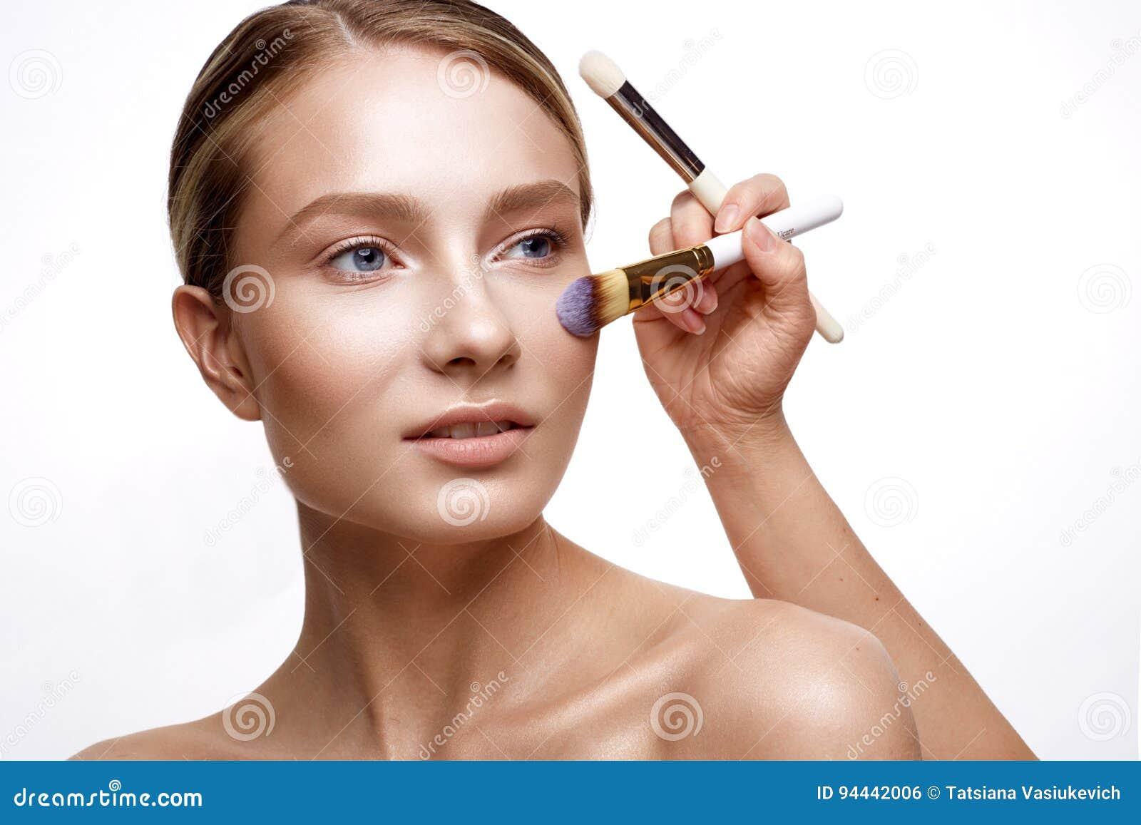 Ung flicka med perfekt glänsande hud- och nakenstudiemakeup En härlig modell med ett fundament och borstar för kosmetiska tillväg