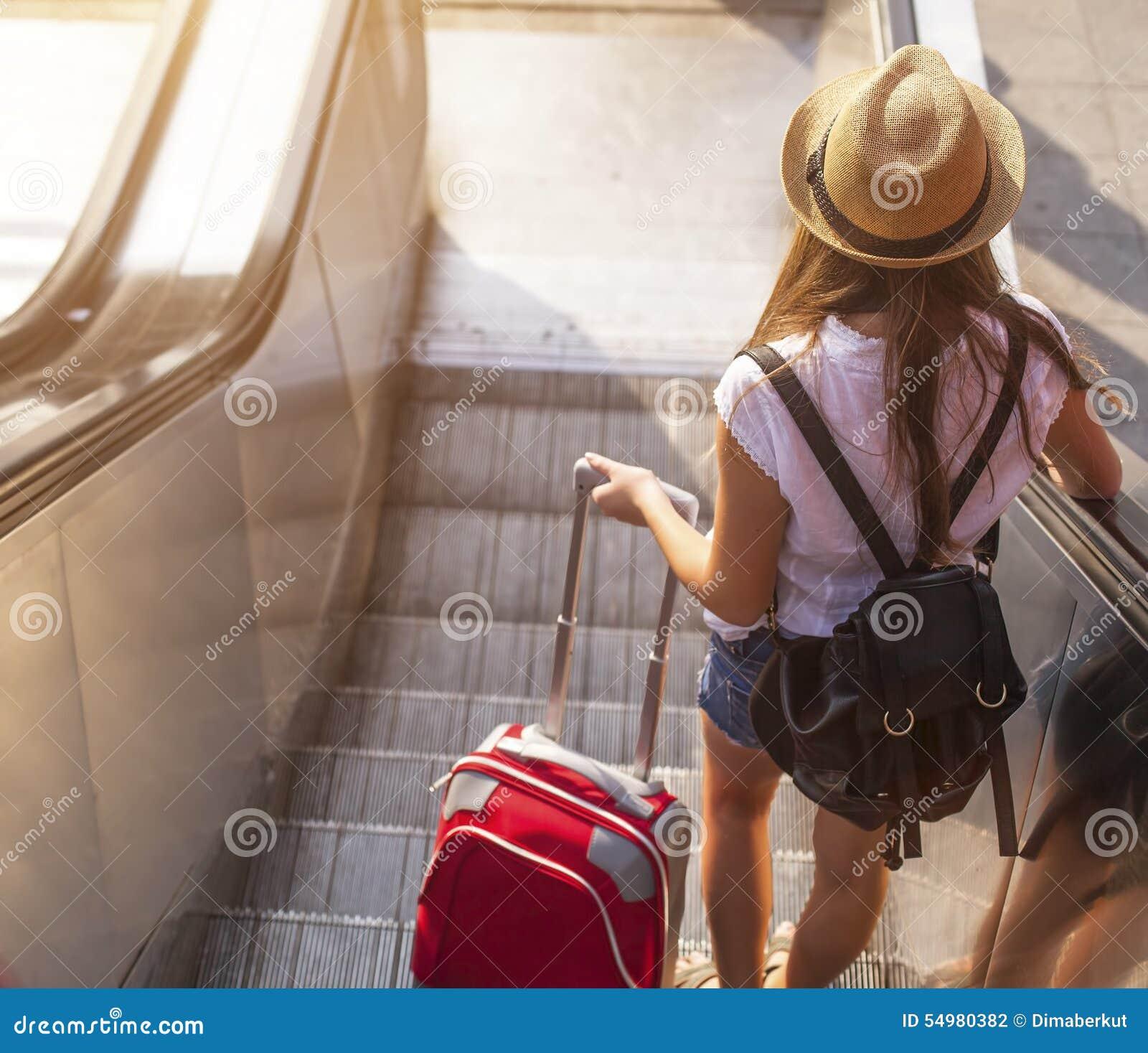 Ung flicka med resväskan ner rulltrappan lopp