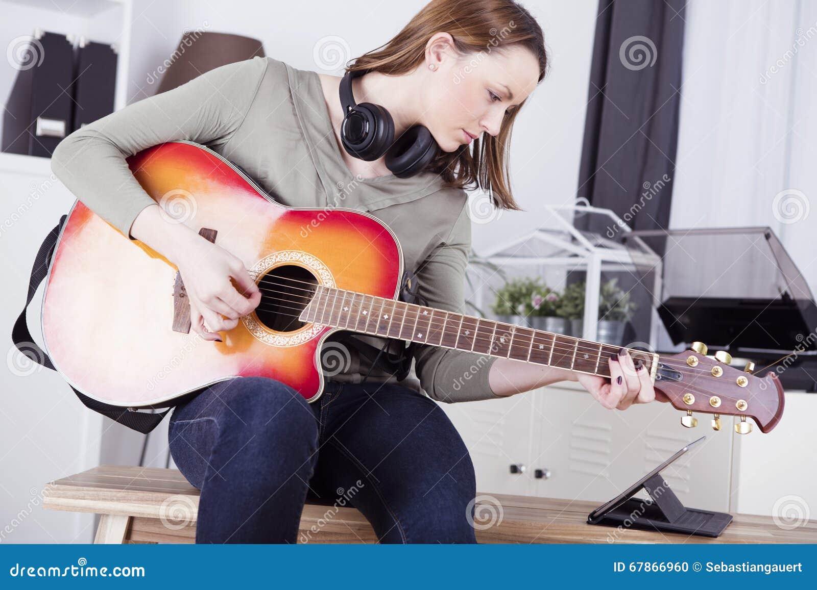 Ung flicka på soffan som spelar gitarren