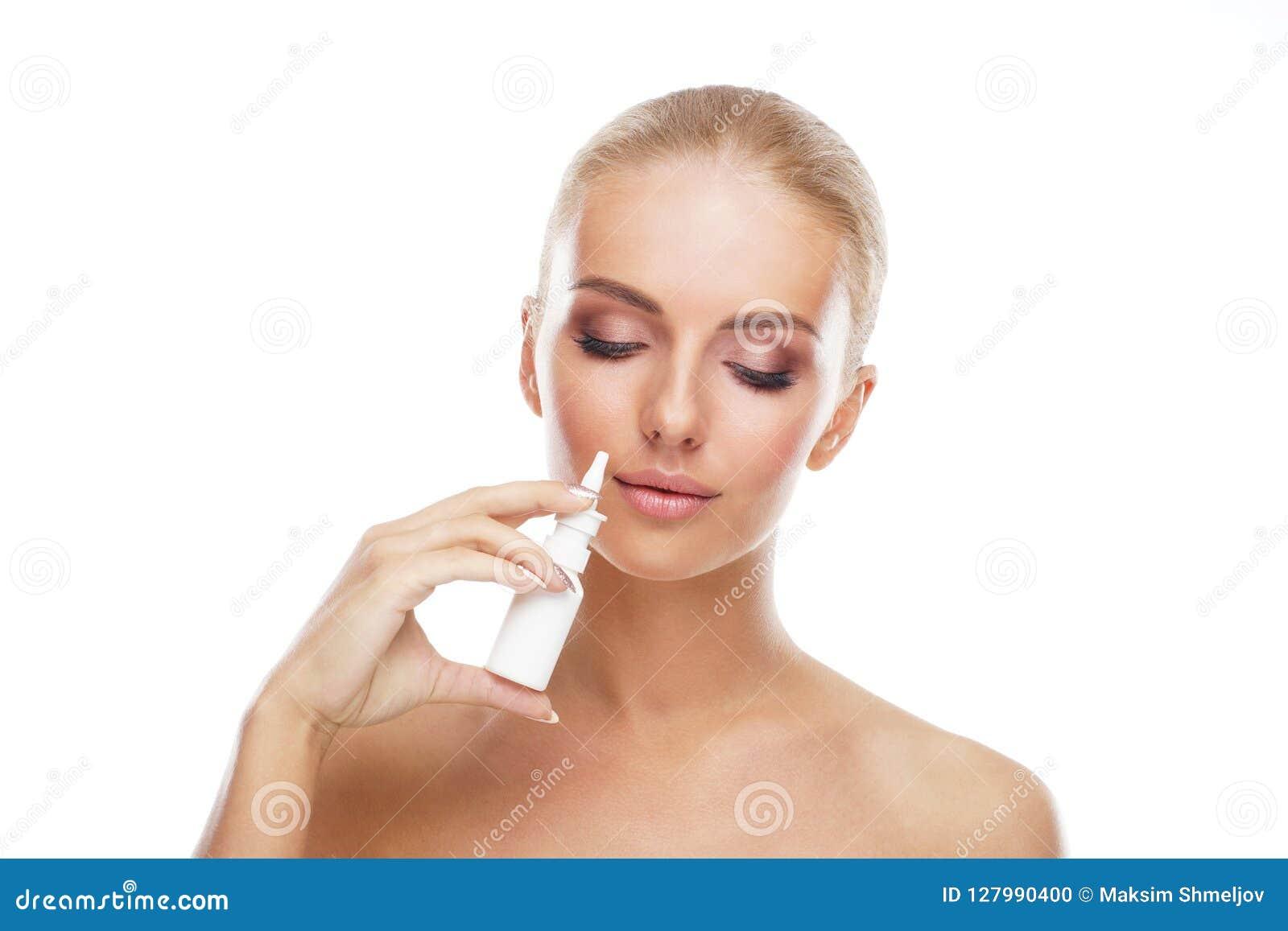 Ung flicka som använder nosal sprejærosol, och droppar som isoleras på vit Sjukdom för rinnande näsa, allergi-, förkylning- och i