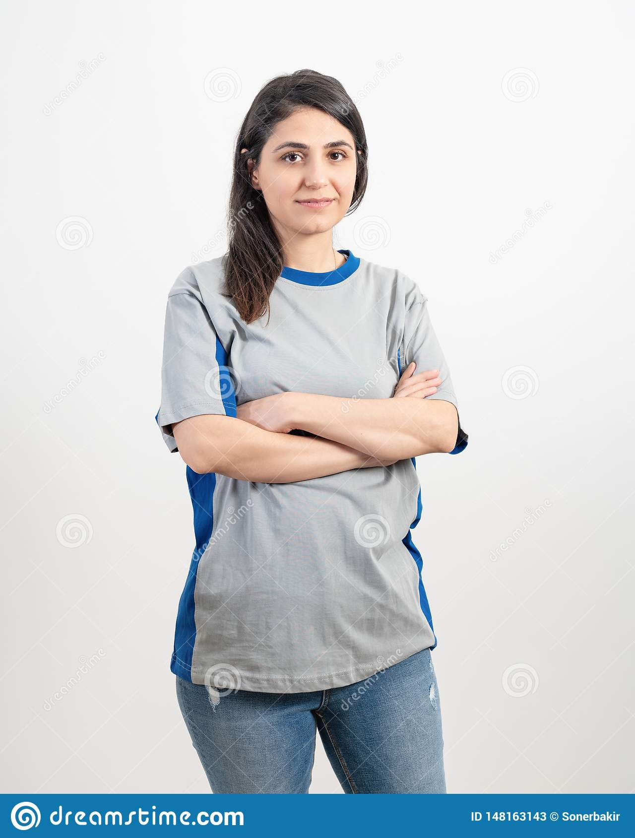 Ung flicka som bär den tomma gråa t-skjortan och jeans Gr? v?ggbakgrund