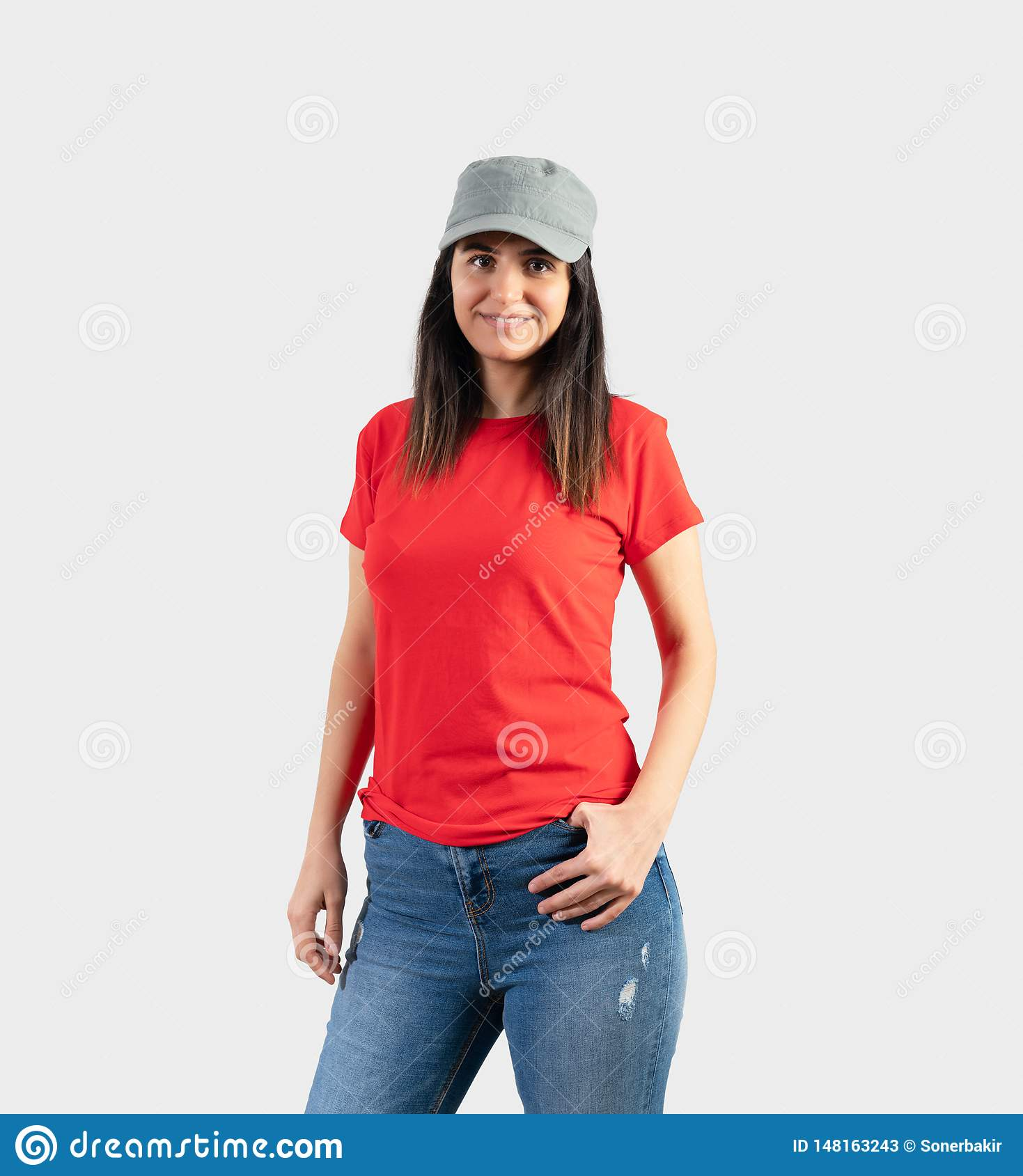 Ung flicka som bär den tomma röda t-skjortan, locket och jeans Gr? v?ggbakgrund