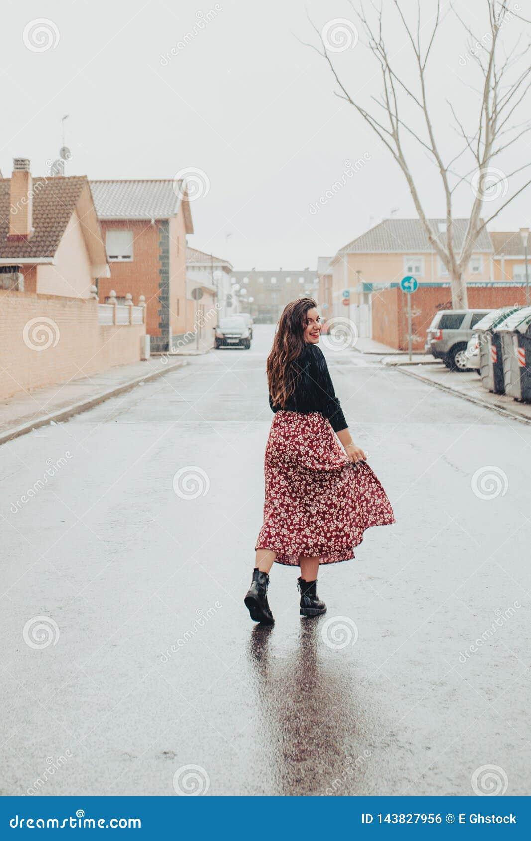 Ung flicka som bl?ter hennes kjol och ler i regnet med svarta k?ngor och den utskrivavna l?nga kjolen