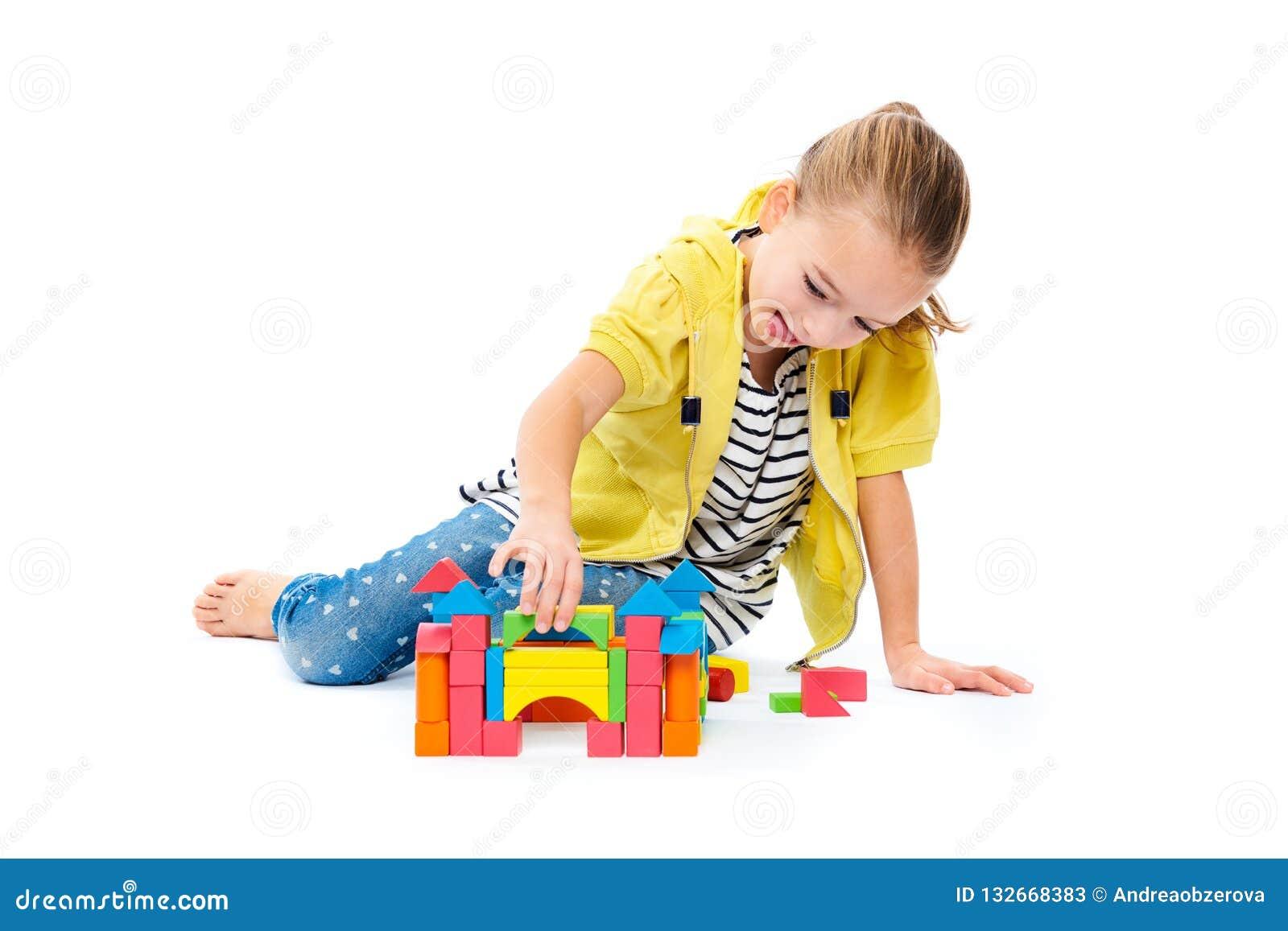 Ung flicka som bygger en slott med träleksakkvarteret Begrepp för terapi för barnlek på vit bakgrund