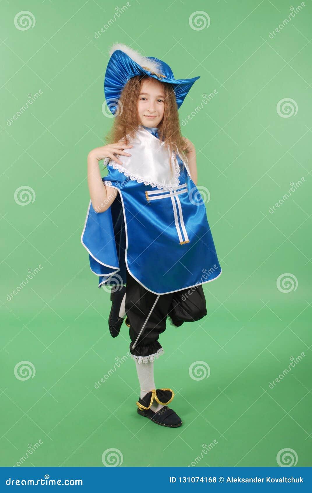 Ung flicka som en musketör i blå dräkt med den älskvärda blåa hatten med fjädrar