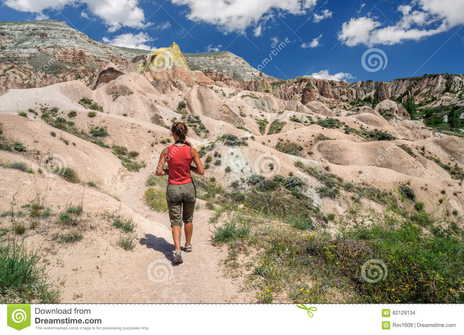 Ung flicka som går i den röda dalen av Cappadocia