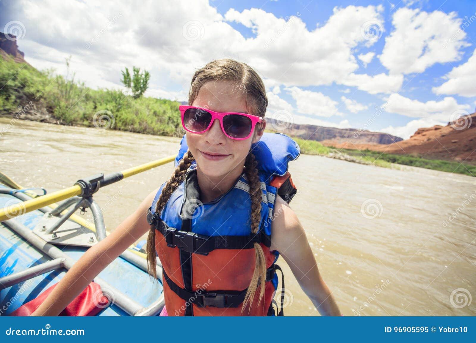 Ung flicka som har gyckel på en tur för rafting för flod ner Coloradofloden