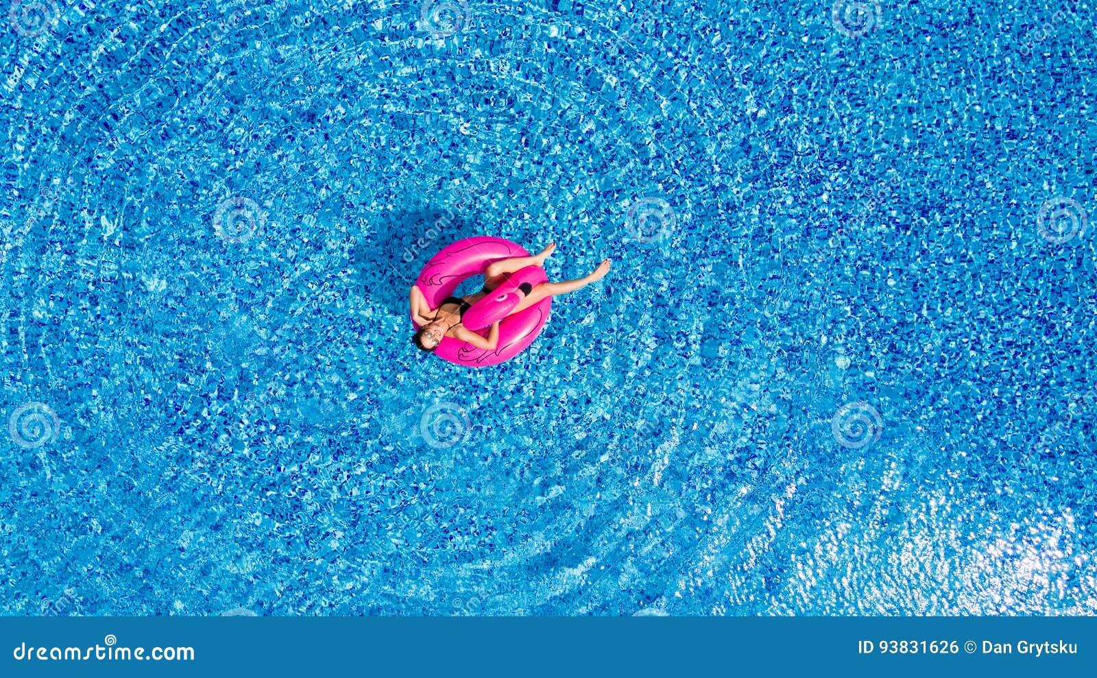 Ung flicka som har roligt och skrattar och har gyckel i pölen på en uppblåsbar rosa flamingo i en baddräkt i sommar från abov