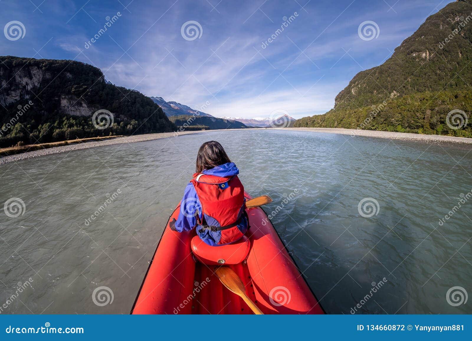 Ung flicka som kayaking ner en pilflod av Nya Zeeland