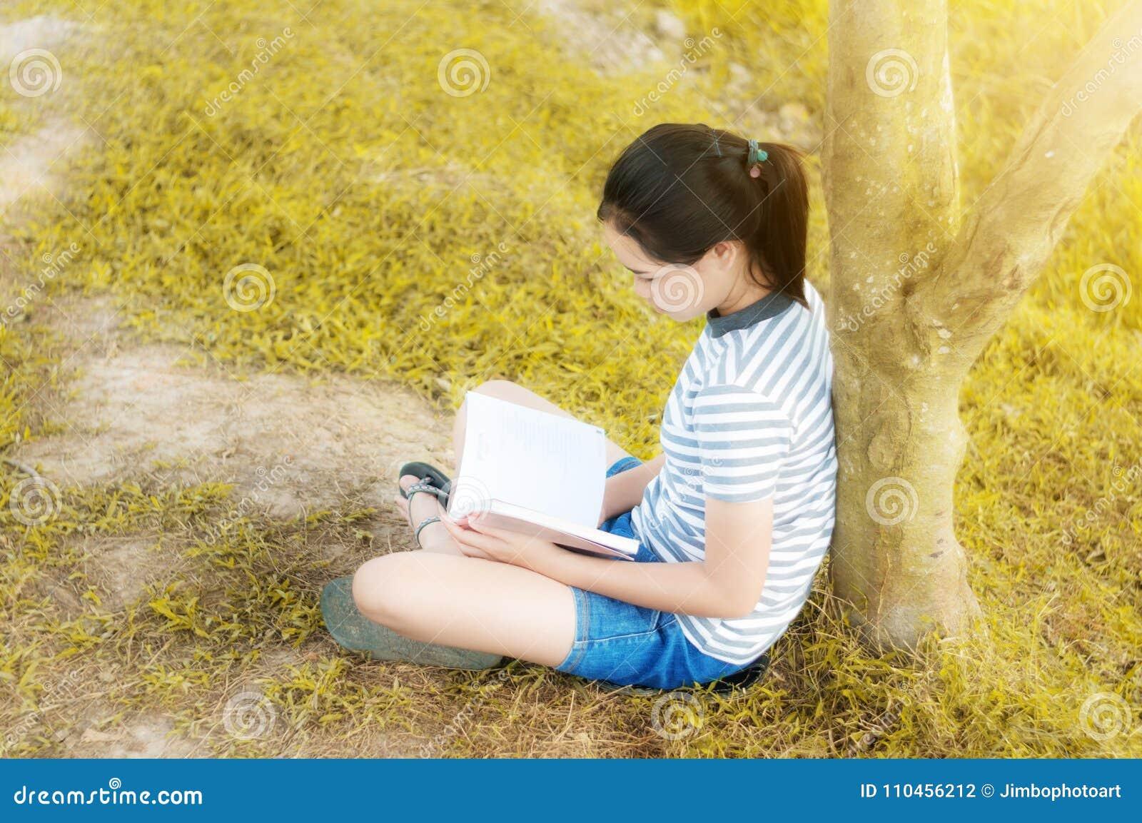 Ung flicka som läser en bok i guld- ängcontrysidenatur