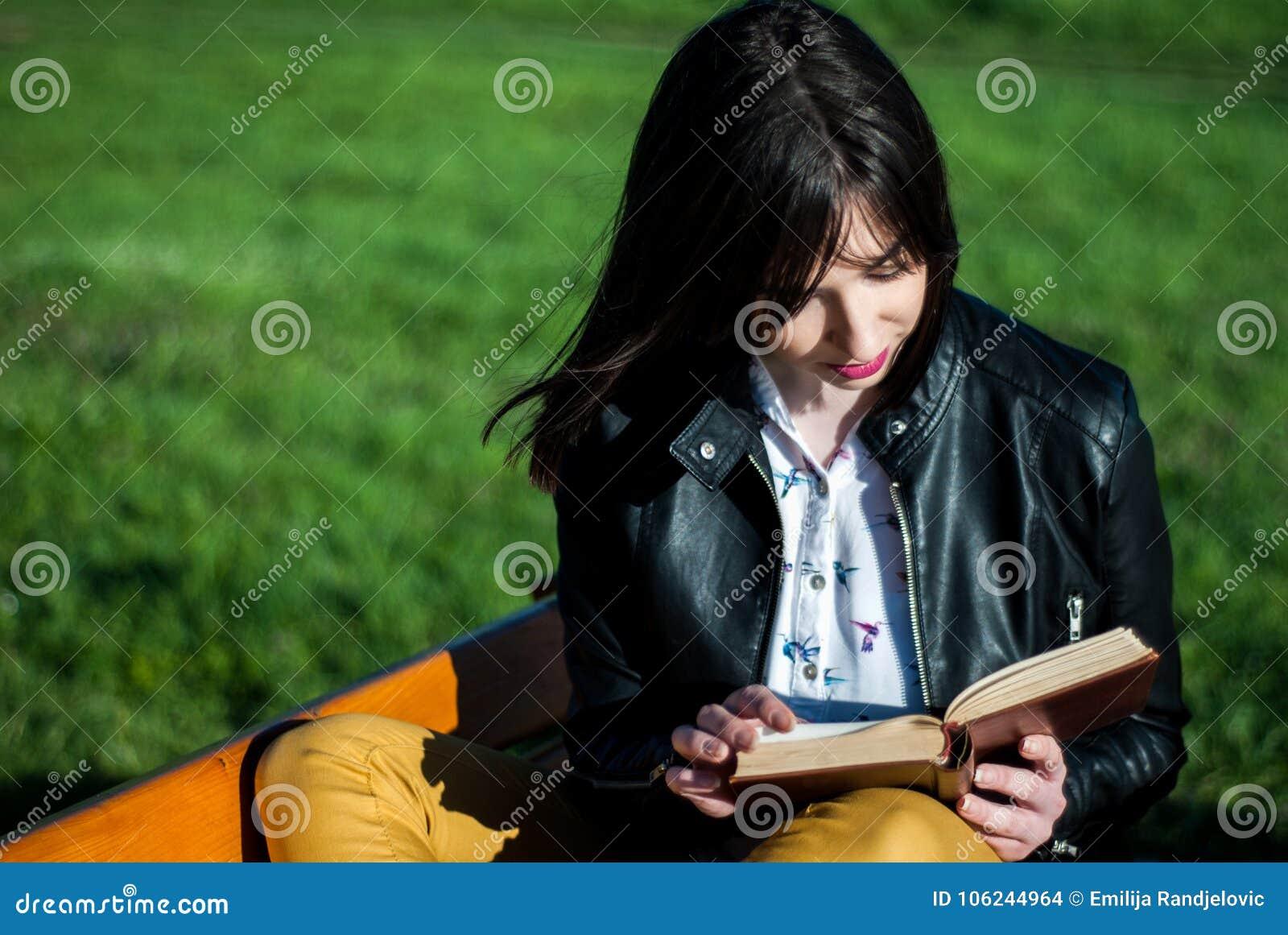 Ung flicka som läser en bok på en solig dag för vår på en bänk i natur