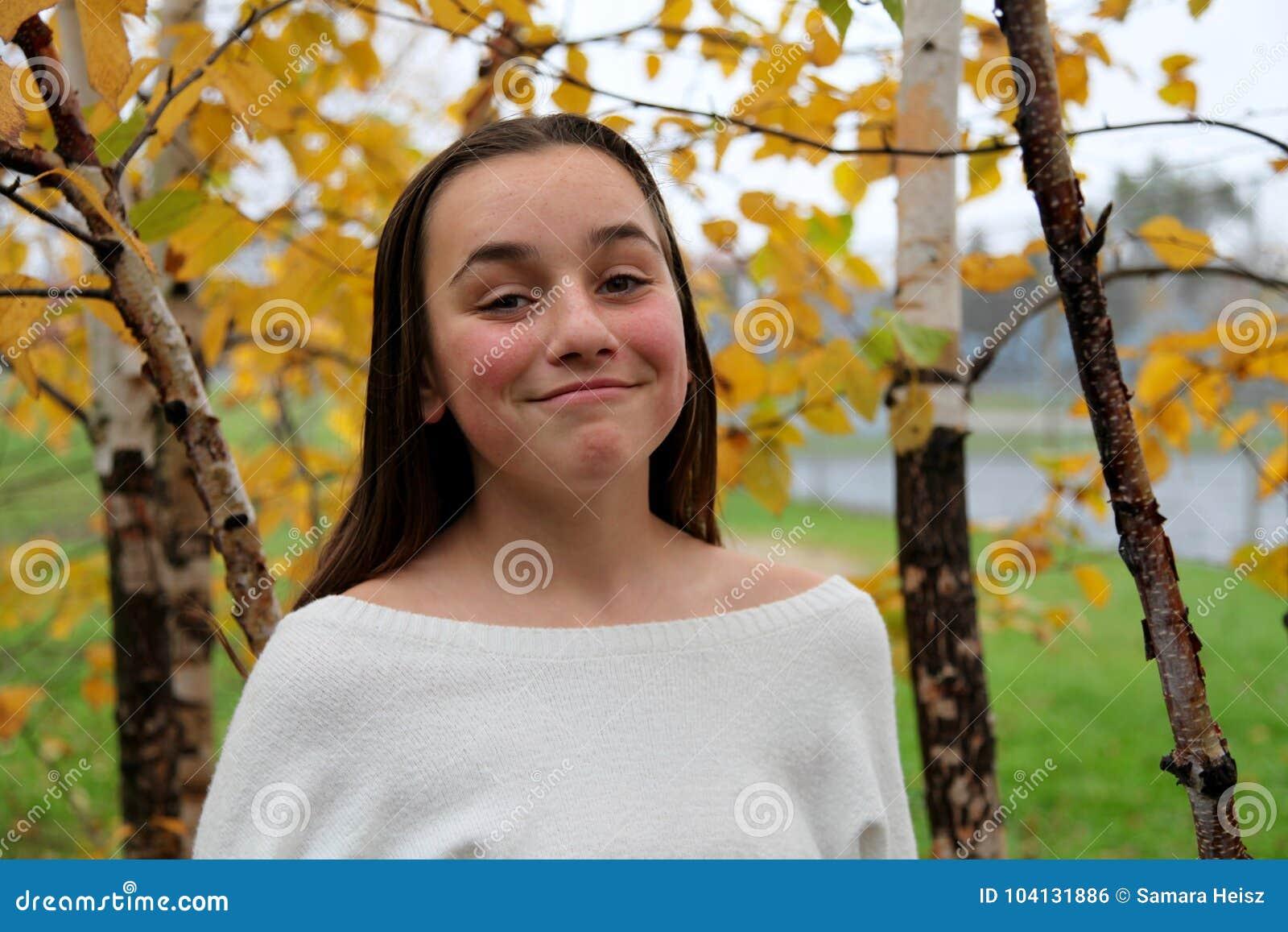 Ung flicka som ler i ett mest forrest av björkträd