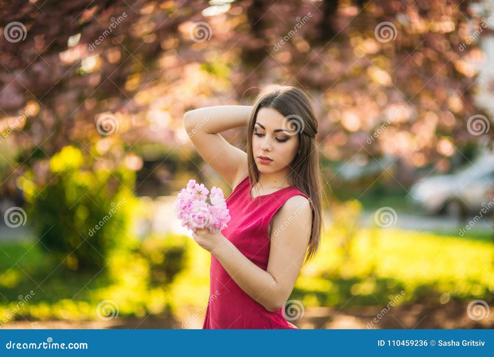 Ung flicka som poserar för ett foto Rosa träd för blomning i bakgrunden Vår Sakura