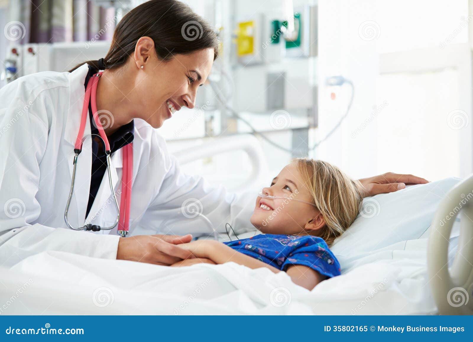 Ung flicka som talar till den kvinnliga enheten för doktor In Intensive Care