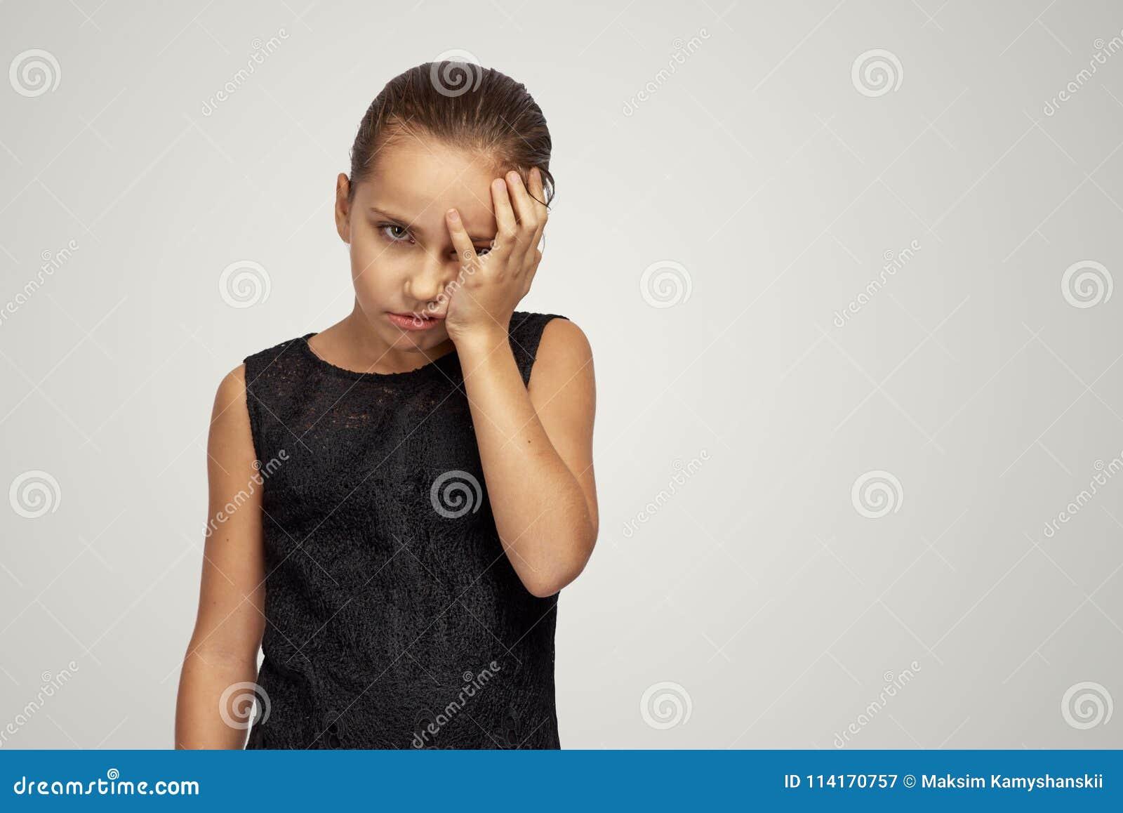 Ung flickablickar som förargas på kameran och, stänger hennes framsida med hennes hand i skam Begrepp av fel, förlust, frustratio