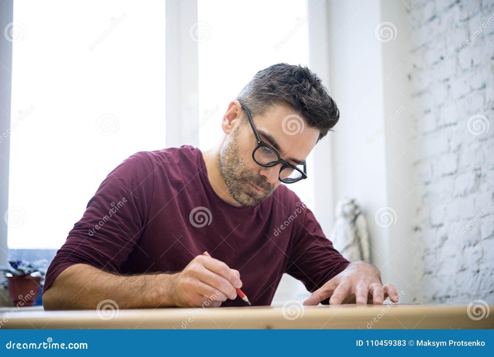 Ung formgivare Drawing skissa genom att använda blyertspennan på trätabellen i ljus studio