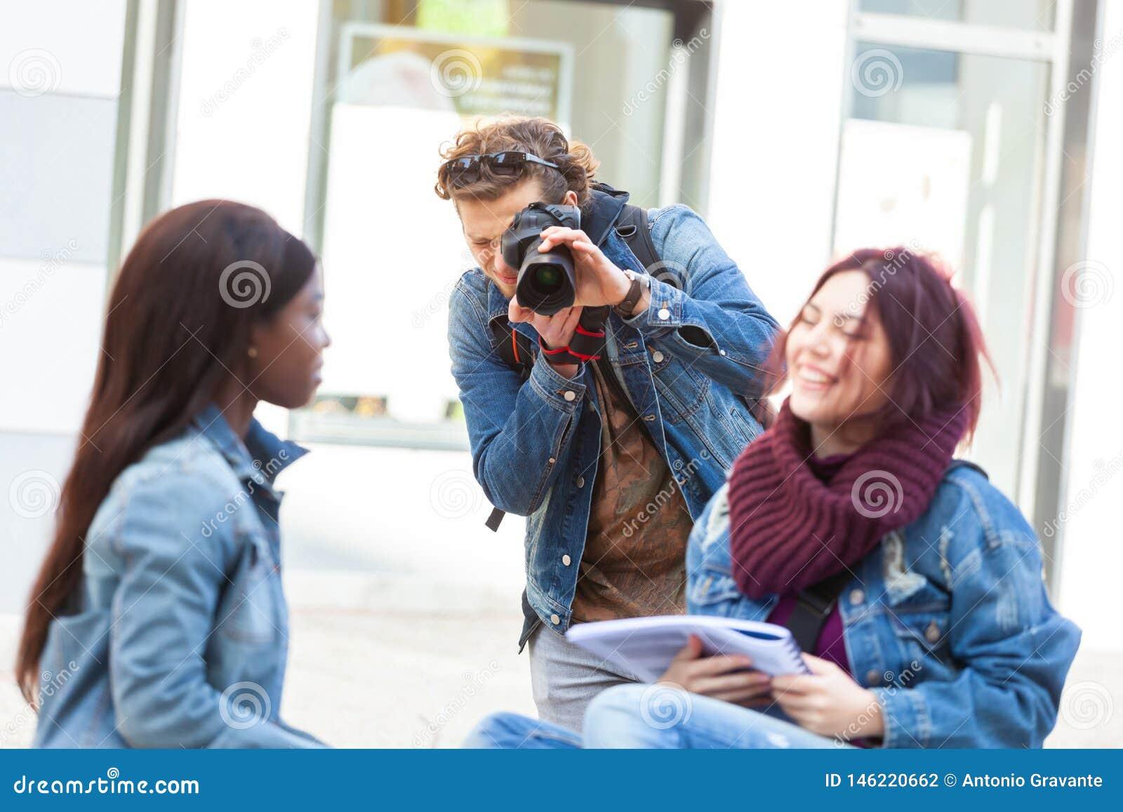 Ung fotograf som tar fotografier av två flickor, medan studera