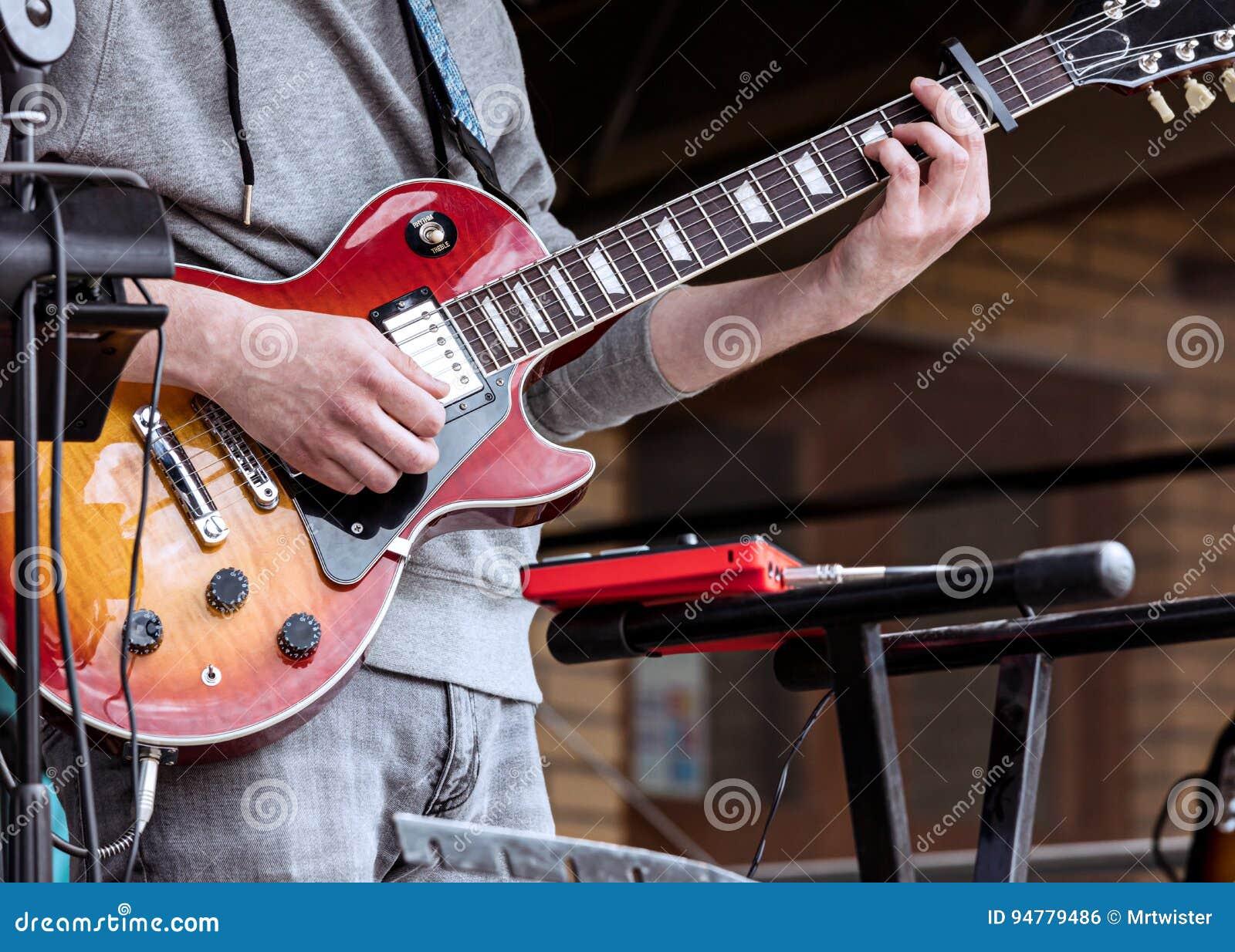 Ung gitarrist som utför på utomhus- etapp under levande konsert