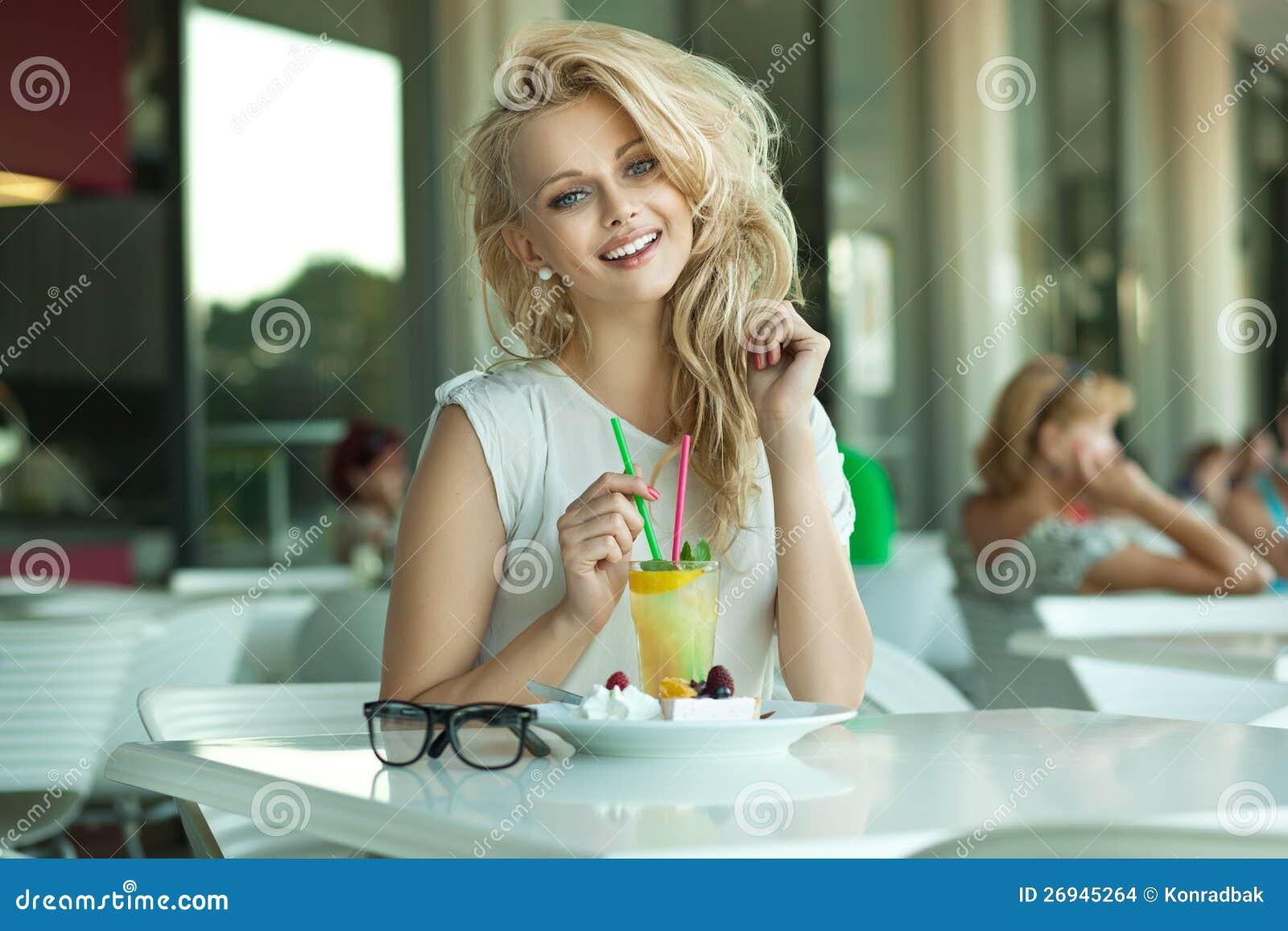 Ung gladlynt blondin i en drinkstång