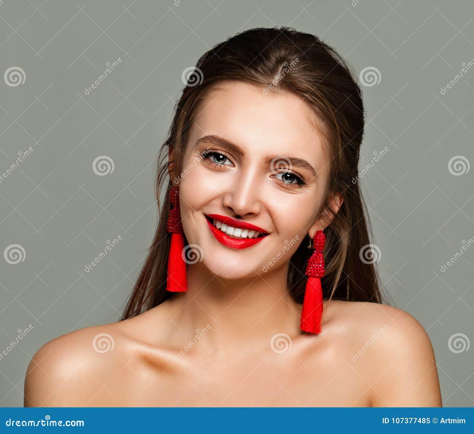Ung gladlynt kvinna med röd kantmakeup och smyckenörhängen