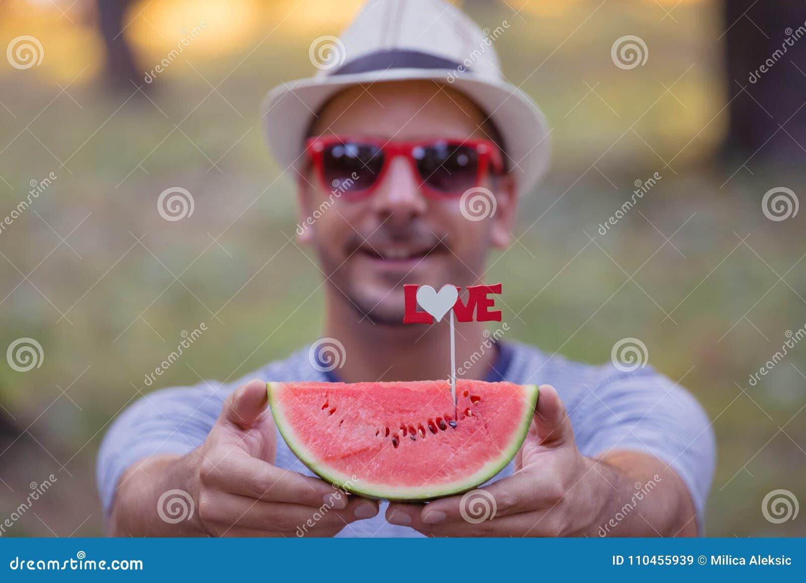 Ung grabbinnehavskiva av vattenmelon med förälskelsetecknet