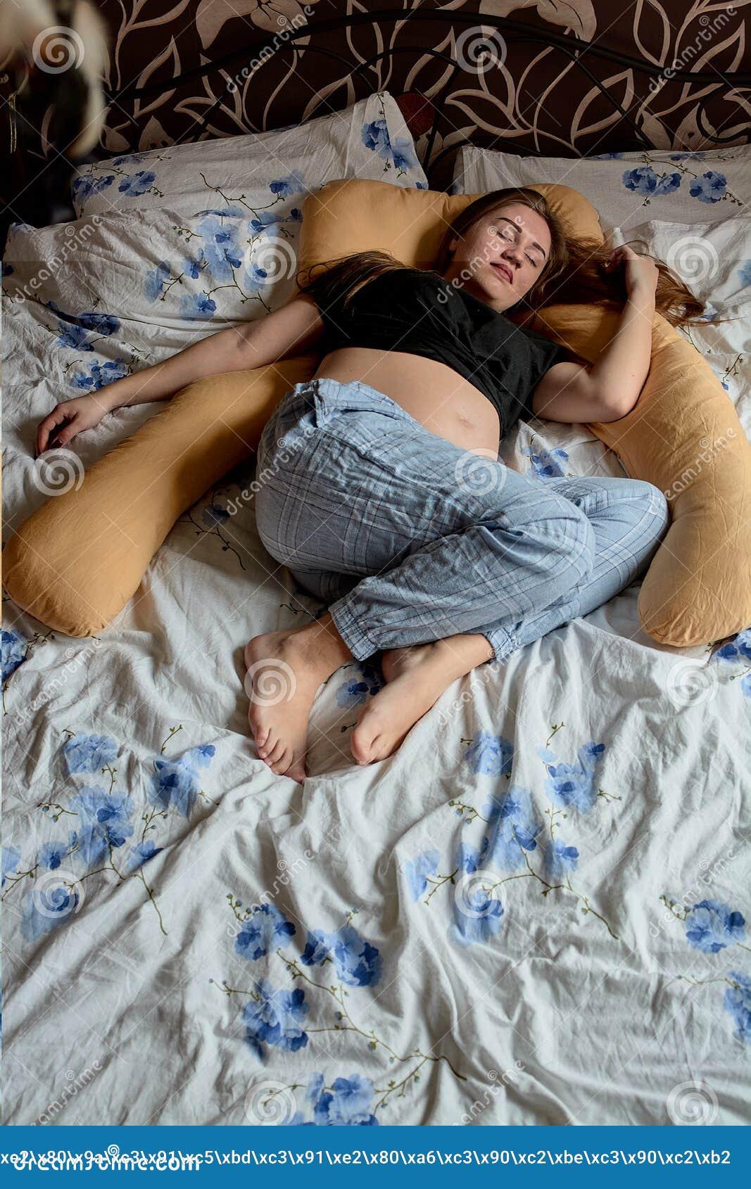 Ung gravid kvinna Den gravida h?rliga kvinnan sover p? moderskapkudden i s?ng