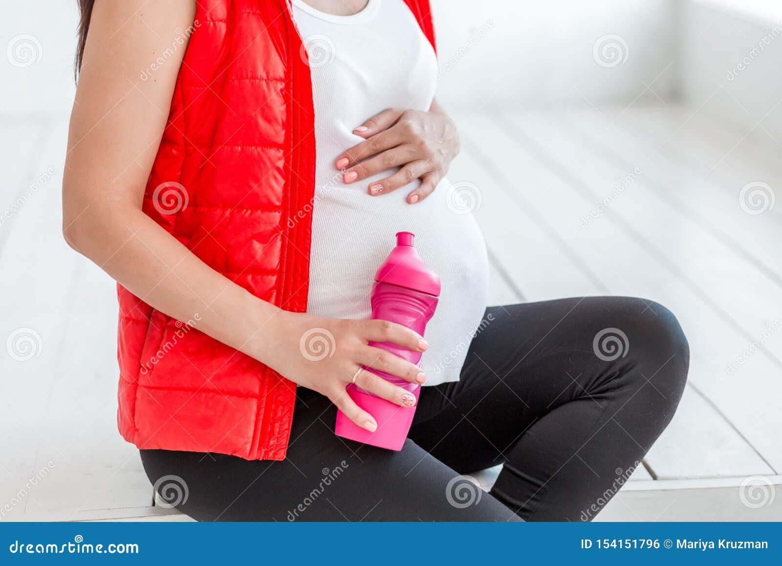 Ung gravid kvinna efter flaska för konditionwhithvatten Sport under havandeskap
