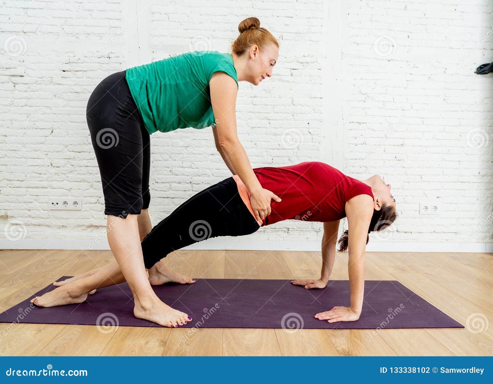 Ung härlig övning för dambörjanyoga med hemmastadd grupp för privat lärare som utarbetar med yrkesmässig kvinnlig yogi