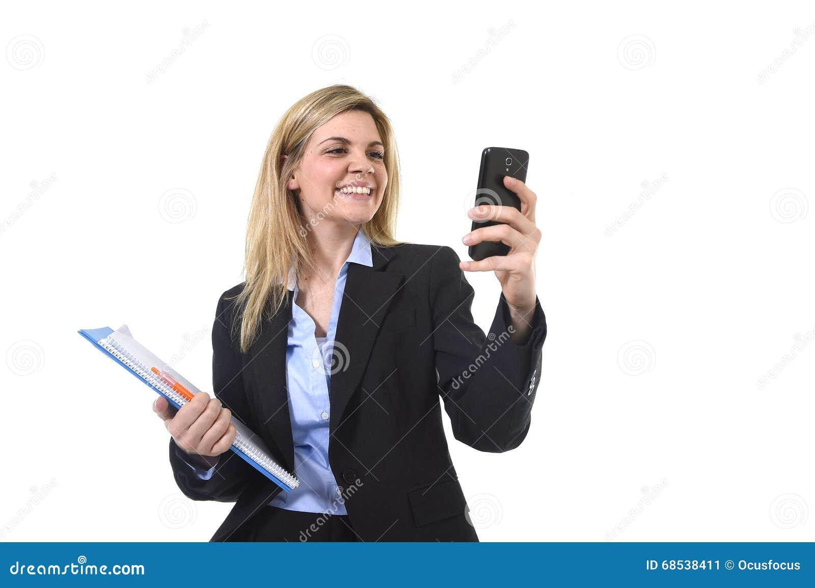 Ung härlig affärskvinna för blont hår som använder internet app på för för kontorsmapp och penna för mobiltelefon som hållande le