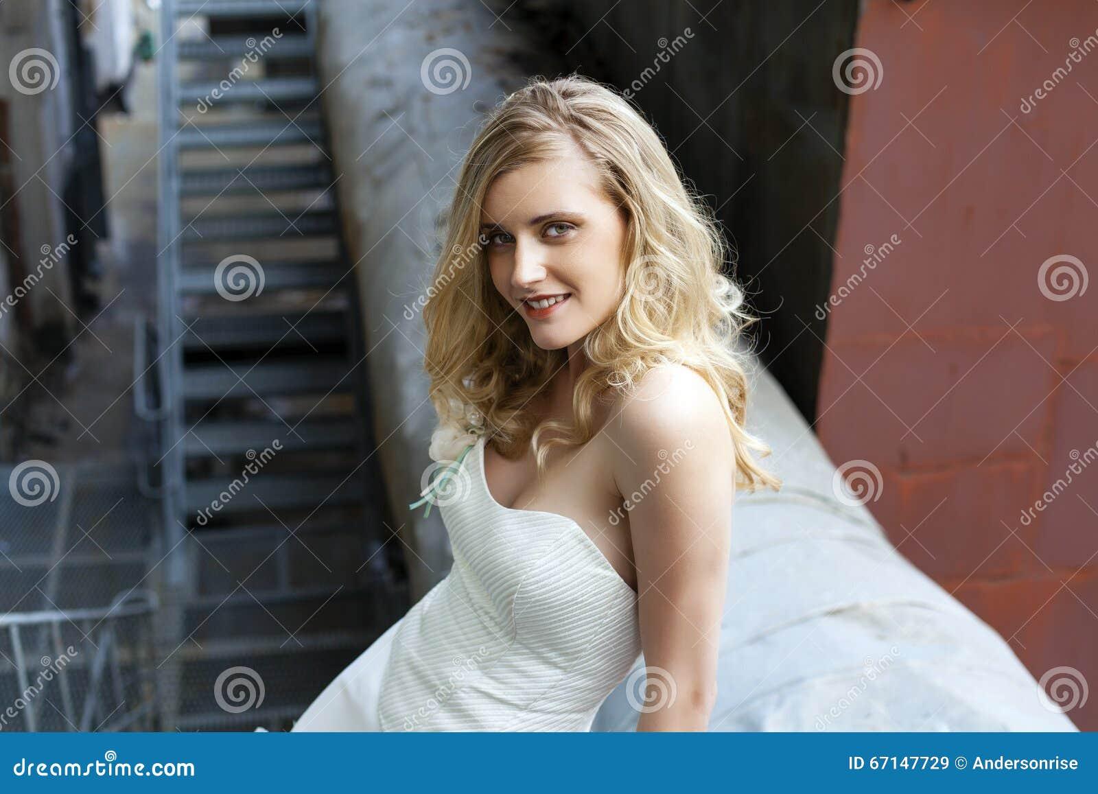 Ung härlig blond kvinna i brud- klänning