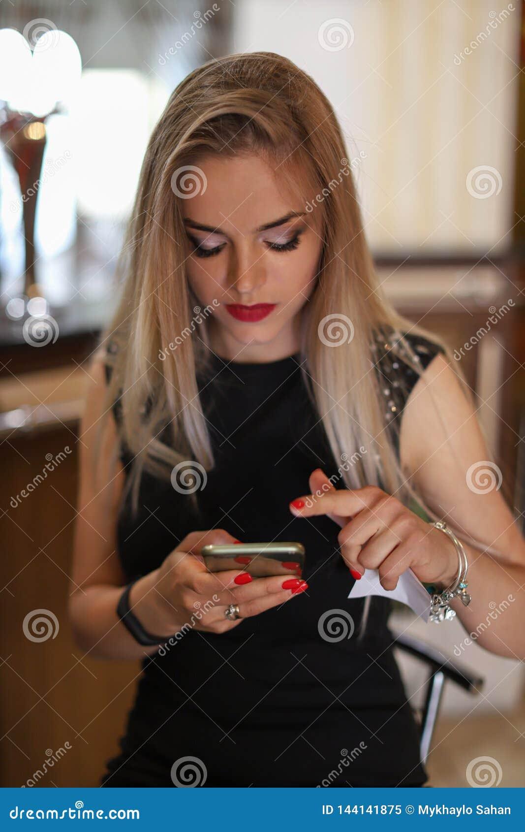 Ung härlig blond kvinna som direktanslutet skriver eller läser smsmeddelanden på en smart telefon i en restaurang Ungt stilfullt