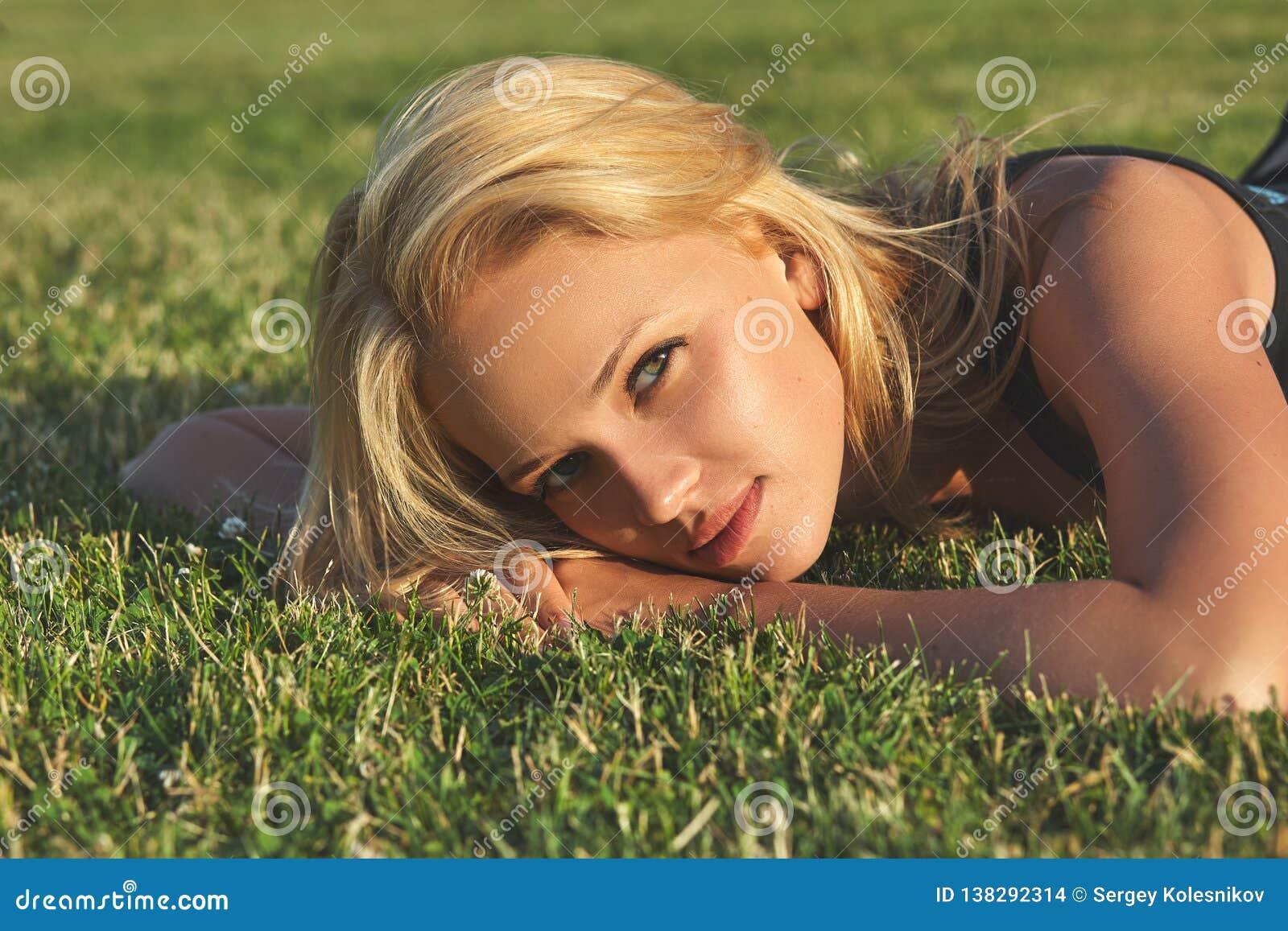 Ung härlig blond kvinna som kopplar av på en äng