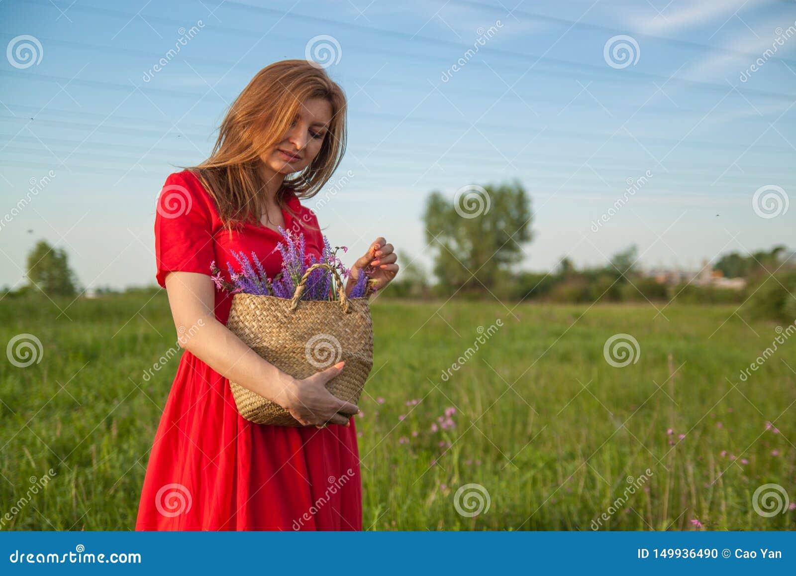 Ung härlig blond kvinna som smilling med blommor i natur i sommaren