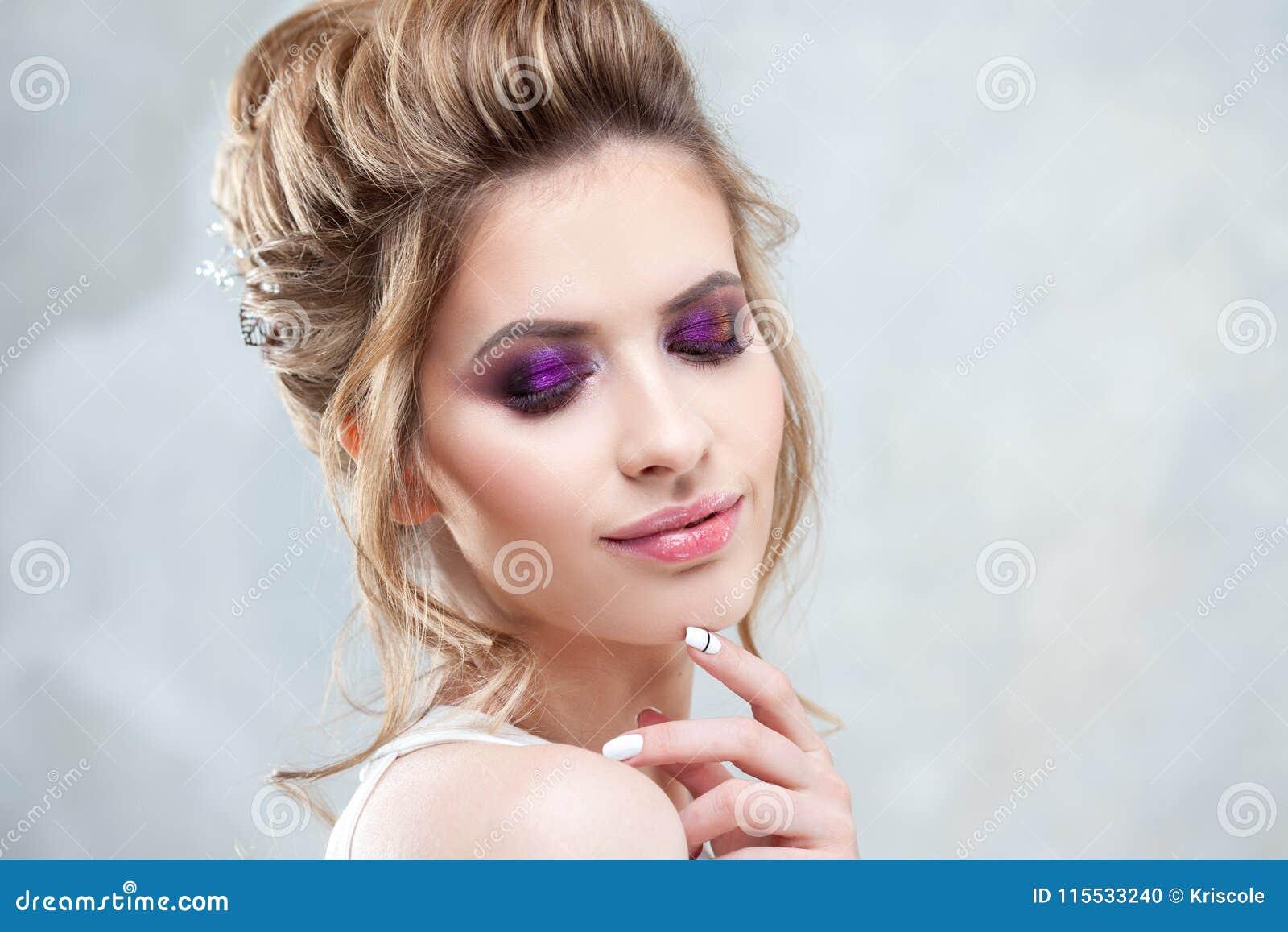 Ung härlig brud med en elegant hög frisyr Bröllopfrisyr med tillbehören i hennes hår