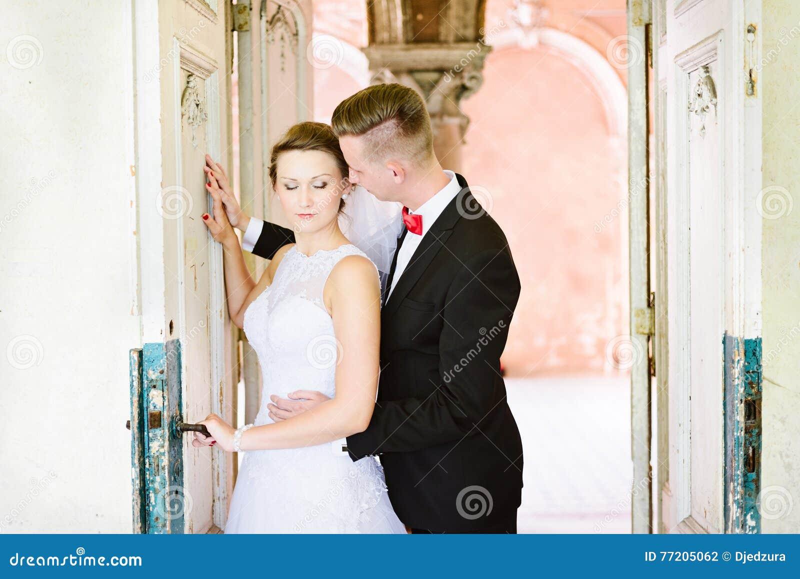 Ung härlig brud och brudgum nära gammal dörr
