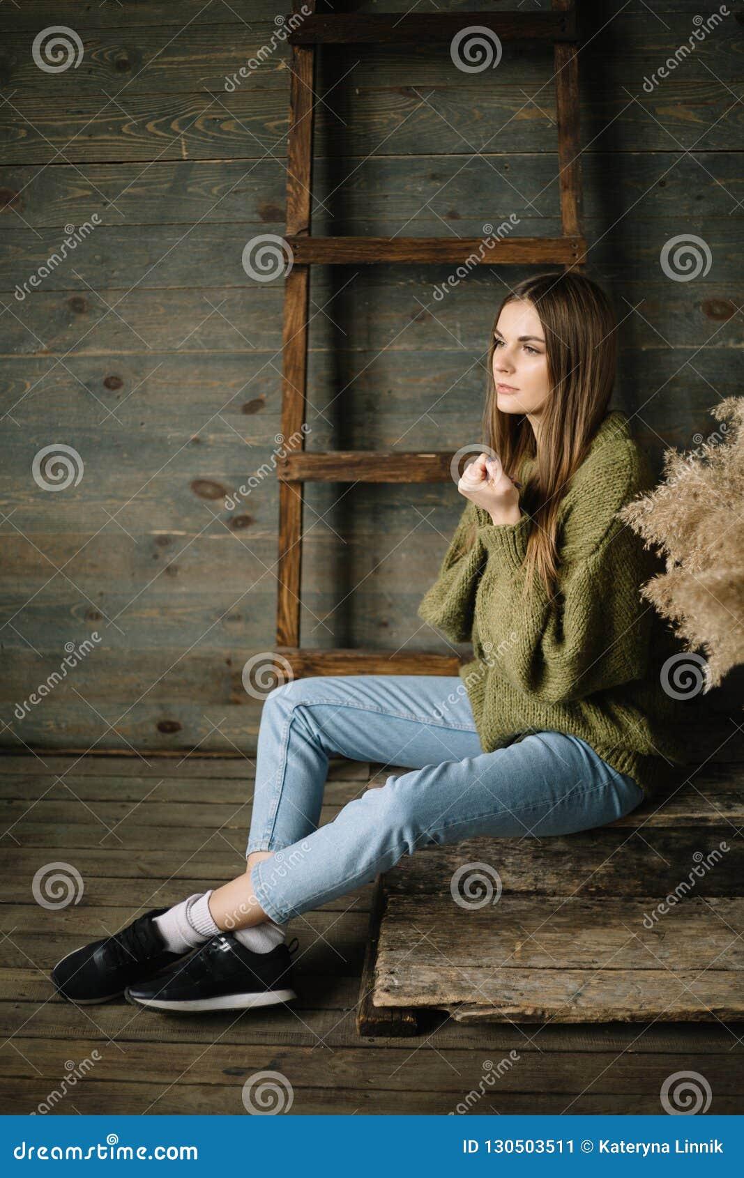 Ung härlig brunettflicka i stuckit ett varmt jeans och gymnastikskor som poserar i studio med dagsljus