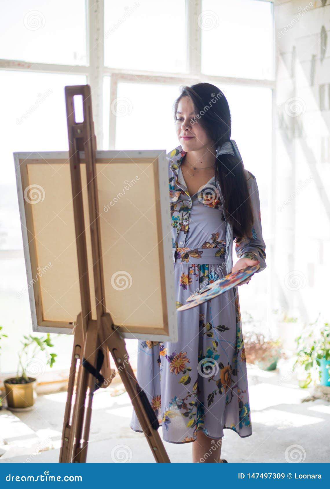 Ung härlig dammålare i klänningen, kvinnakonstnärmålning
