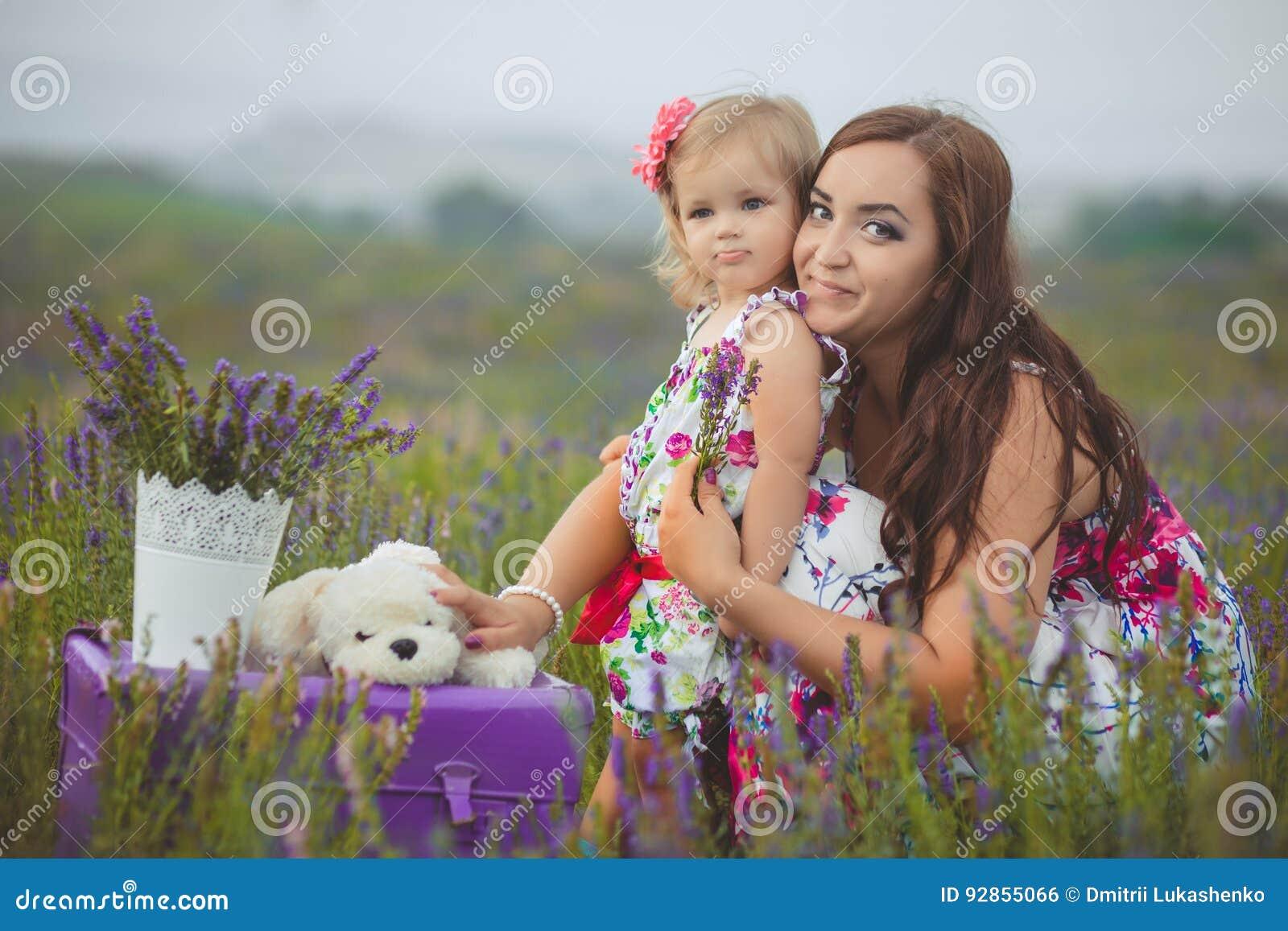 Ung härlig dammoder med den älskvärda dottern som går på lavendelfältet på en helgdag i underbara klänningar och hattar
