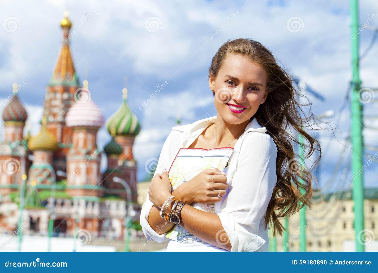 Ung härlig flicka som rymmer en turist- översikt av Moskva