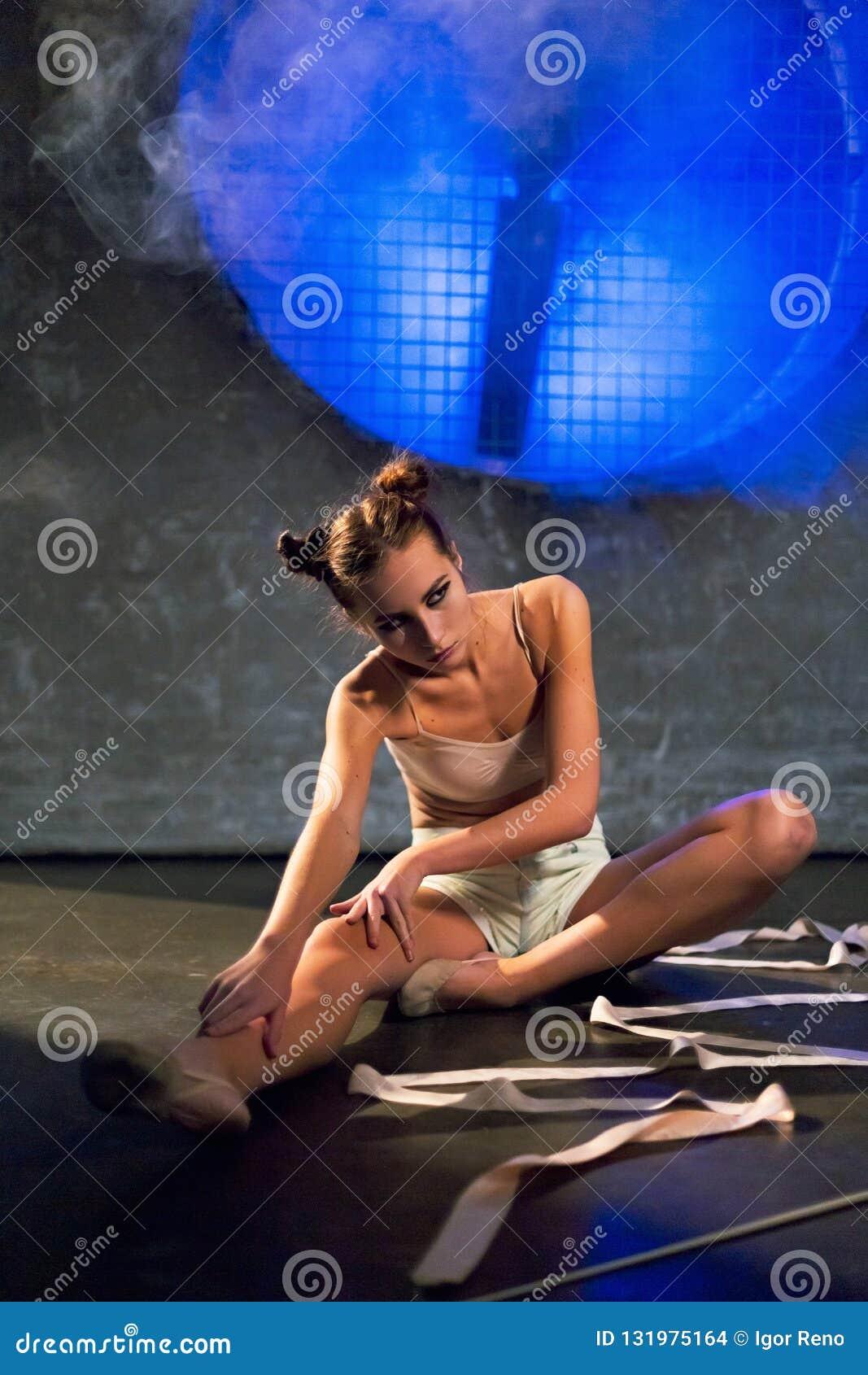 Ung härlig gymnastkvinna som gör sträcka övningar på golvet på idrottshallen