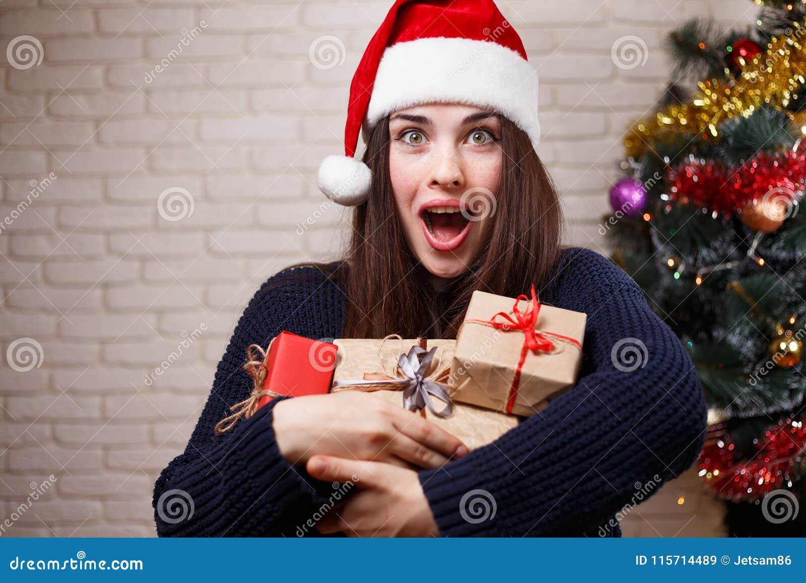 Ung härlig häpen lycklig kvinna i jultomtenlock med många gåva b