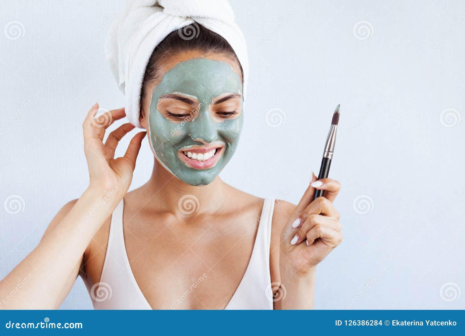 Ung härlig kvinna i framsidamaskering av terapeutisk blå gyttja Spa