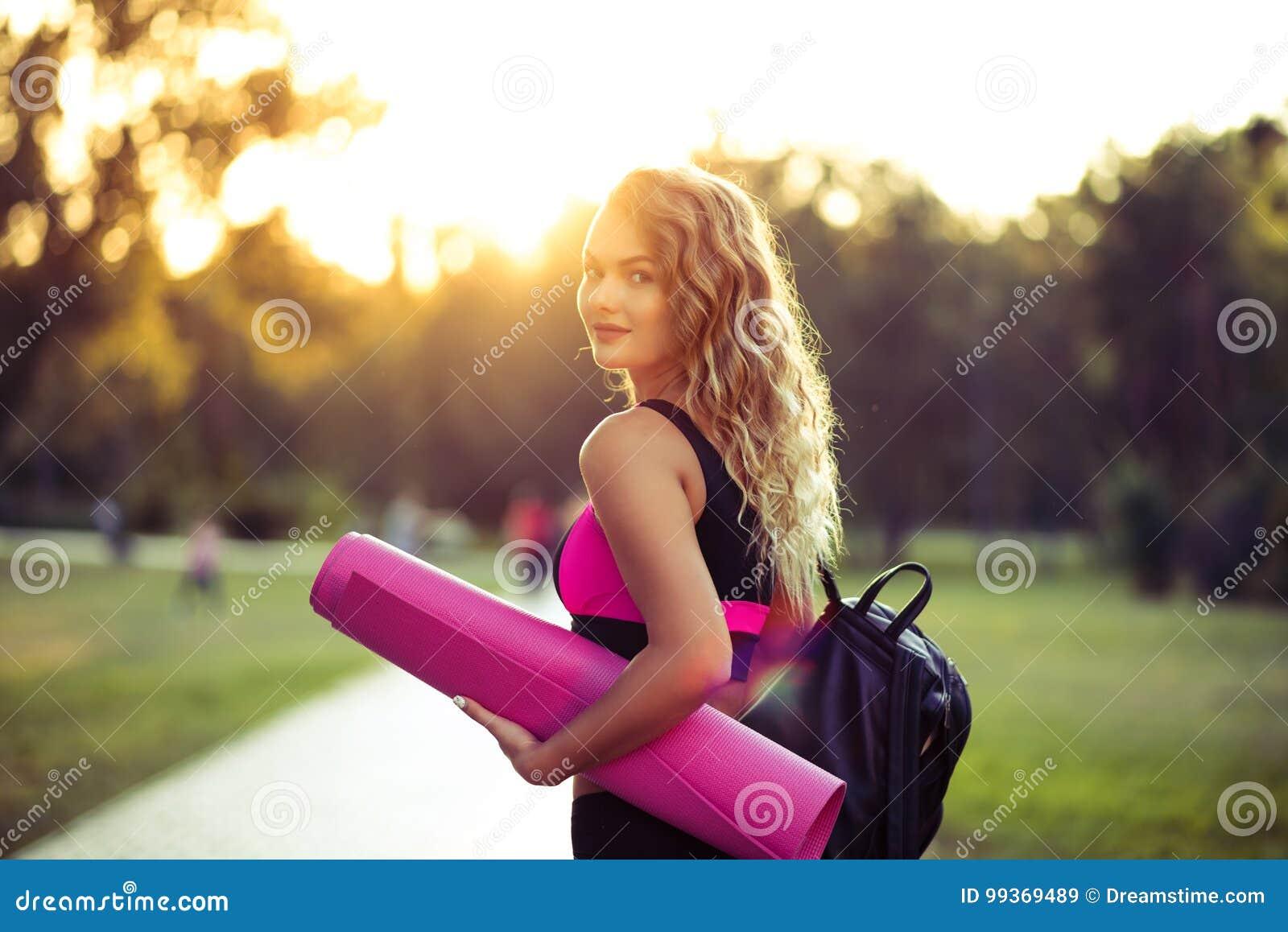 Ung härlig kvinna i sportswear Henne ` s som rymmer en utbildning matt Gå att göra sportar som utbildar, gymnastik utomhus