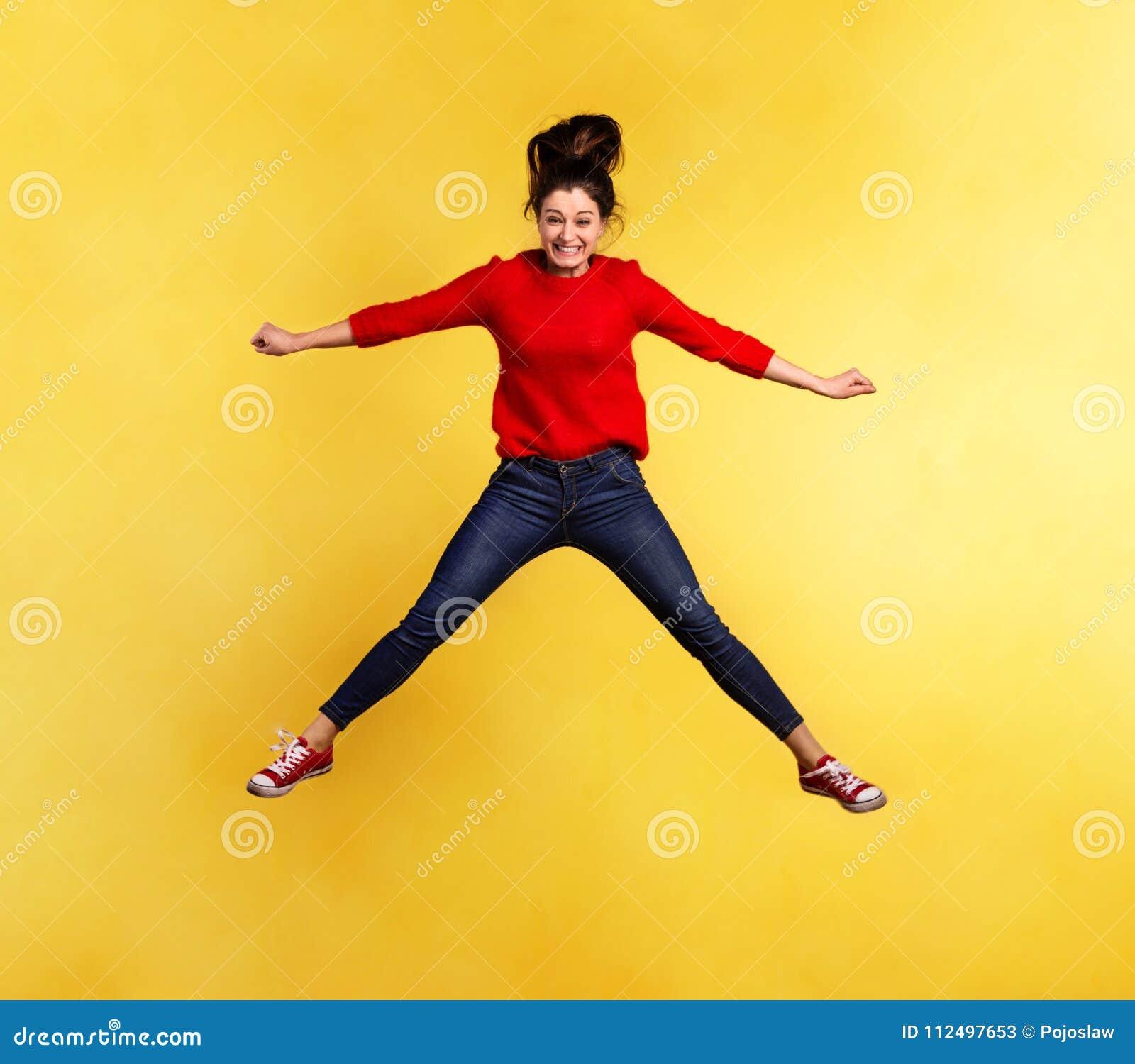Ung härlig kvinna i studion som hoppar