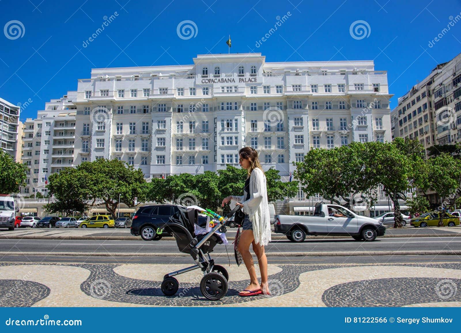 Ung härlig kvinna med barnvagn på bakgrunden av den Copacabana slotten i Rio de Janeiro, Brasilien