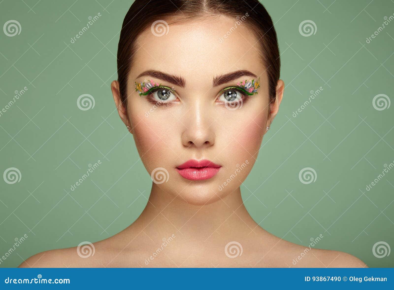 Ung härlig kvinna med blommamakeupögon