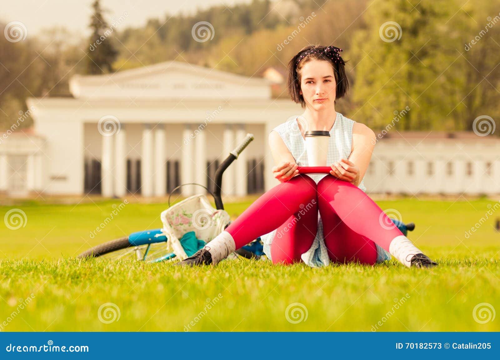 Ung härlig kvinna med bok- och kaffekoppen