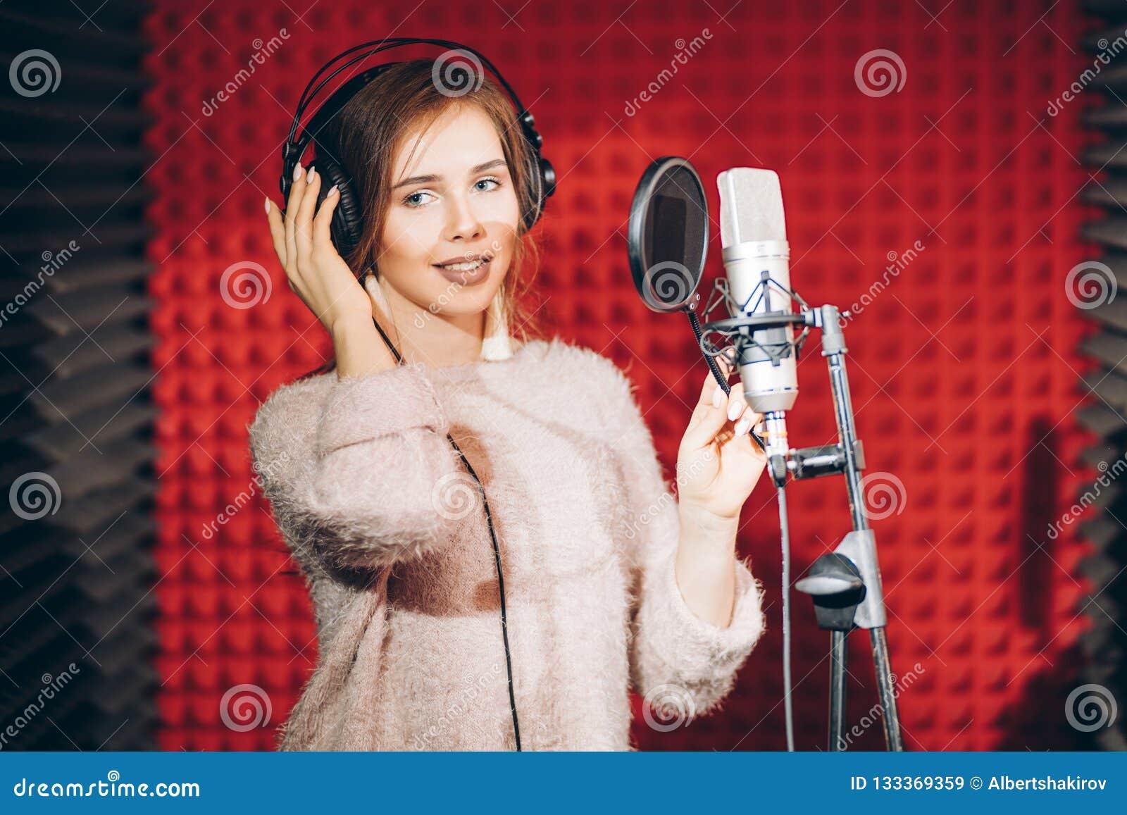 Ung härlig kvinna som antecknar en sång i en yrkesmässig studio med den röda väggen