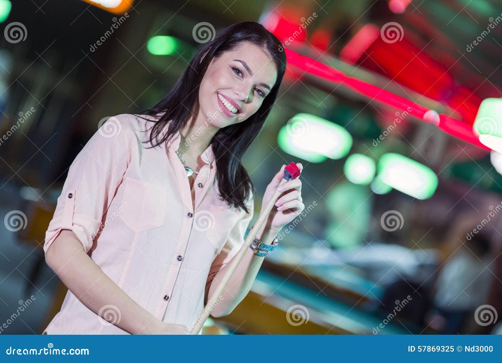 Ung härlig kvinna som chalking stickrepliken och le för snooker