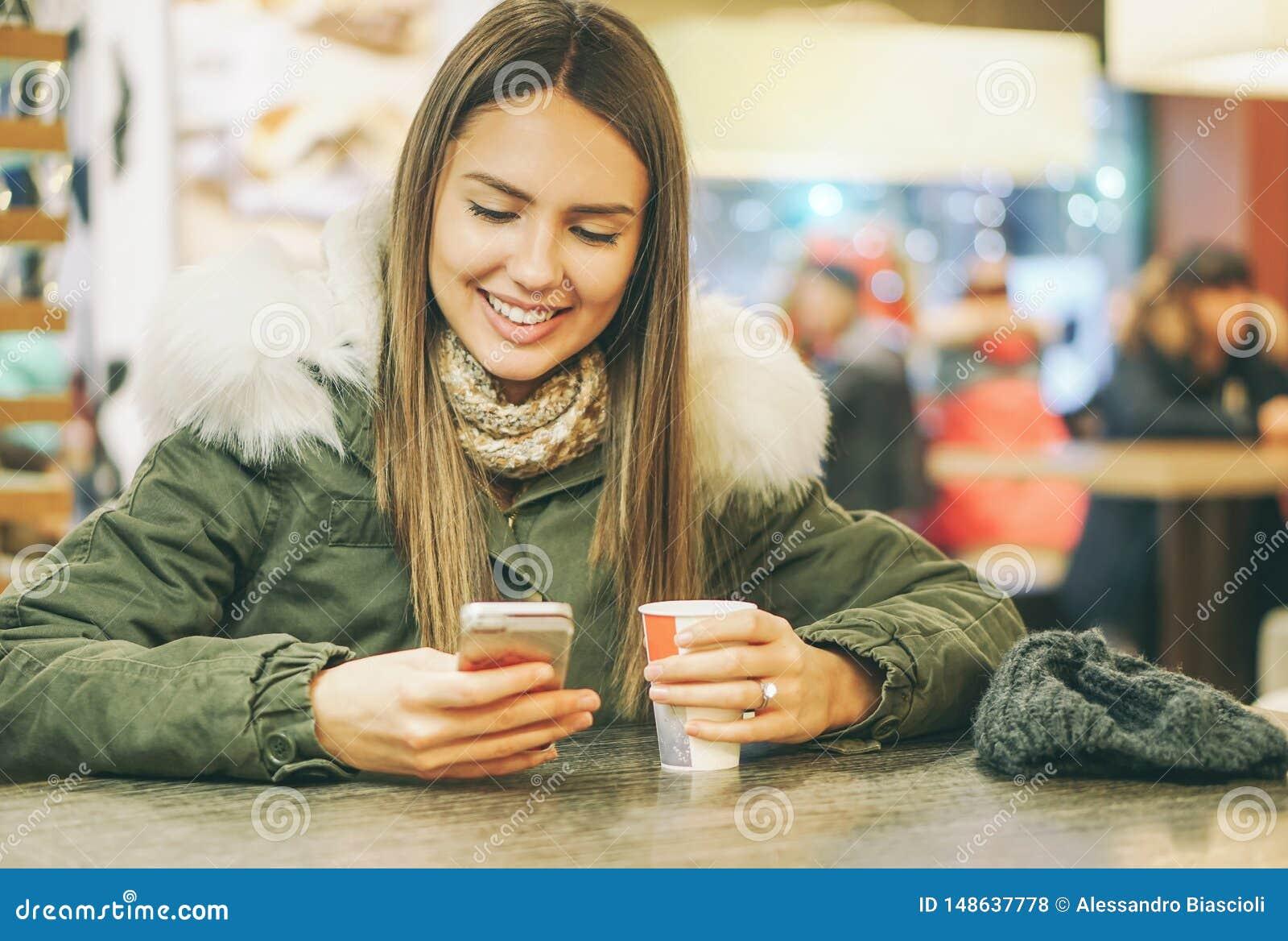 Ung h?rlig kvinna som dricker ett kaffe i en kaf?st?ng, medan skriva p? den mobila smarta telefonen genom att anv?nda applikation